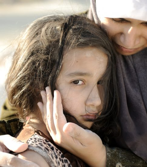 Poverty and poorness on the children face. Sad little girl. Refugee. In Muslim  mother's arms.
