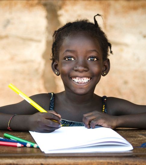 A huge smile on the face of a young school girl sitting in her desk drawing.