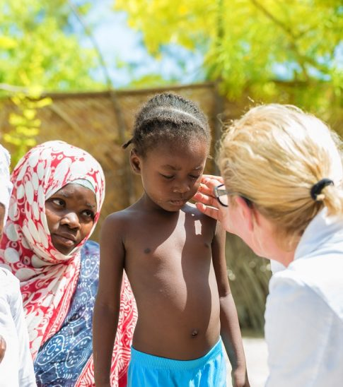 Caucasian female doctor meeting African family with a children.Doctor touching little girl's face